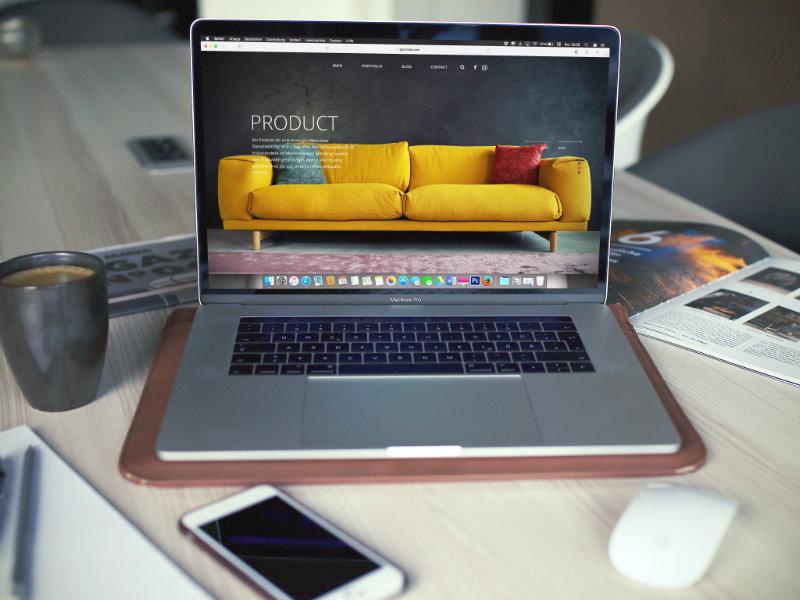 Ordinateur portable Mac ouvert avec un fond d'écran moderne de canapé
